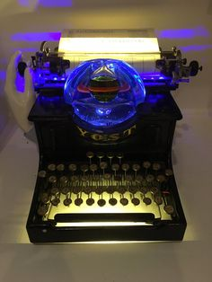 Old French typewriter, hand blown glass magnifies light and color of LEDs.