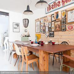 Eine schlichte Holzverkleidung mit bunt zusammengewürfelter Bilderrahmen-Deko belebt das Esszimmer und gibt ihm ein gemütliches Flair. Unterschiedliche Stühle…
