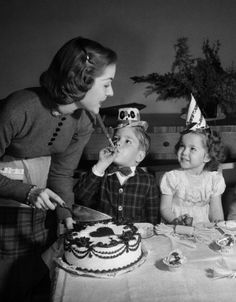 1950s woman mother cutting birthday cake for two children sitting at table wearing party hats