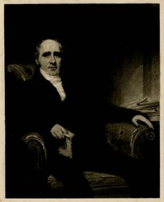 Seated in an upholstered arm-chair, balding, with his finger marking a place in a book and a pile of books on the table beside him; proof before letters.<br/>Mezzotint