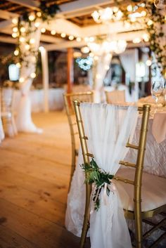 Elegant wedding chair cover idea - gold Chiavari chairs draped in white tulle and greenery {ShoeBox Photography}