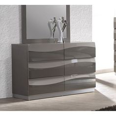 The Delvin 6-drawer dresser features a glossy grey finish to offer a clean, modern look. This piece provides an elegant and functional accent to your bedroom decor.