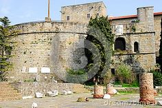 Photo taken to the remains of the Roman forum that is next to the Catholic Cathedral of San Giusto Martire in Trieste in Friuli Venezia Giulia (Italy). In the picture you see, in the foreground, some column elements and partly hidden by a wall tree in regular blocks of stone on which there are two openings and a white stone plaque. To the left of the wall you see another building with a circular base ever built with stones.
