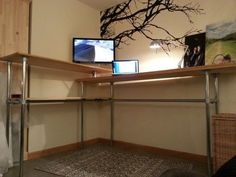 Awesome L-shaped standing desk. Couple wood planks, pipes, and kee klamps - seems easy enough.