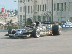 In this photo apparently taken at the 1977 running of the Long Beach grand prix, I believe we're seeing Mario Andretti take a hard right from Pine Avenue north to Ocean Boulevard east, in the John Player Special car. Remnants of the Pike, and the still-with-us Ocean Center Building may be seen in the background.