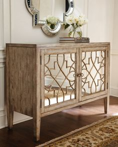 Handcrafted of hardwood solids, laminated lumber, and veneers with mirrored glass. Hand-painted parchment finish with gold-painted highlighting and physical distressing. Two doors with fretwork overla