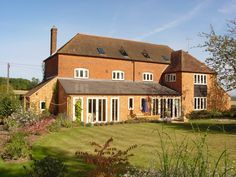 French doors and windows with radius heads add character to this barn style home Timber Windows, Windows And Doors, Surrey, Joinery, French Doors, Barn, London, Mansions, House Styles