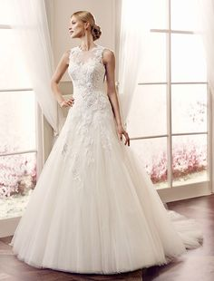 This a line princess style wedding dress is fitted to low hip and flares into a tulle skirt while the bodice has a high neckline at front and back and is covered in lace appliques. Available in ivory