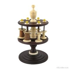 """Turned mahogany 1- tier rotating thread spool holder sewing stand. Central turned ivory column with urn shaped finial. Six wire spindle pins with yellow glass bead tops hold a variety of bone spools, including two carved spools. DATE:1850 - 1860 SIZE:8"""" x 4.25"""" dia. CONDITION:Good. No chips or dings to the wood. Ivory and bone have darkening. Ivory column does have split lines. Spool Holder, Thread Holder, Thread Spools, Beaded Top, Sewing Box, Wood Turning, Glass Beads, Candle Holders, Carving"""