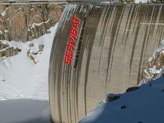 Location et installation des plateformes suspendues sur un barrage hydraulique avec un hélicoptère pour le levage et l'approvisionnement du matériel.