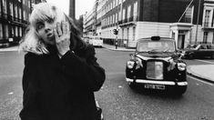Debbie Harry of Blondie poses next to a distinctive London taxi in 1977