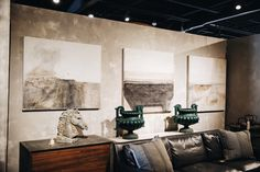 The beautiful abstract paintings of Paul Meyer in our showroom, with bright splashes of jade in a pari of antique urns. Georgia Brown Home Houston.