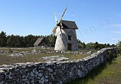 Traditional landscape on Gotland Island. Stone wall and wind mill in Fårö.