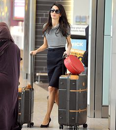 Mrs. Clooney stepped out in a ladylike black and white dress ensemble, featuring a checkered print collar by Oscar de la Renta. She paired the look, reminiscent of Jackie O, with huge round sunglasses and black pointy-toe pumps.