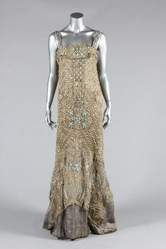 An opulent be-jewelled orientalist cloth of silver evening gown, probably Callot Soeurs, 1907 and altered in the 1920s, columnar with gold embroidered filet lace over-dress studded with cabochon turquoise stones and pearls, the hem with deep band of Egyptian papyrus blooms.