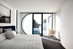 This modern bedroom features a half-circle window that's frosted to provide some privacy without blocking the light. Click through to see more photos of this modern house. #ModernBedroom #Windows #CurvedWindow #BedroomDesign