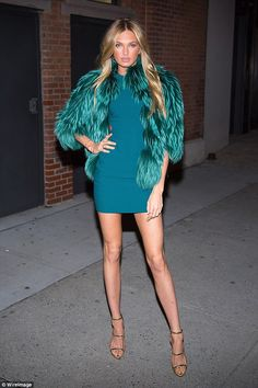 Green with envy:Clad in a sensational teal getup, the 21-year-old Dutch model flashed her endless pins in a simple-yet-chic mini dress paired with an edgy fur coat in the same colour