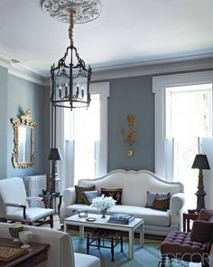 POETIC LICENSE    A vintage French sofa and an 18th-century English armchair, both upholstered in muslin, in the living room; the Georgian-style lantern is bronze, the tole lamps are vintage, the 1920s French sconce is by Armand-Albert Rateau, and the Spanish gilt-wood mirror is a New York flea-market find.
