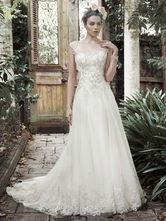 Exquisite patterns metallic embroidered lace adorn the decadent bodice of this A-line wedding dress; complete with full tulle skirt; edged in lace. Stunning illusion cap-sleeves grace the shoulder; cascading into a scoop neckline and V-back. Finished with crystal buttons and zipper closure.