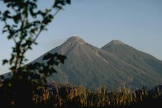 Fuego (left) and Acatenango are two of several paired volcanoes in Guatemala. Southward-younging volcanism constructed these two large stratovolcanoes and flank vents perpendicular to the trend of the Guatemalan volcanic front. The chemistry of lavas also varied progressively from dominantly andesitic at Acatenango to increasingly basaltic at Fuego. Activity from the Pleistocene-Holocene Acatenango has continued only sporadically into historical time, but Fuego is one of the most active…