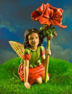 """Geranium Fairy Figurine - $13.95  A lovely vibrant colorful fairy figurine to brighten up your miniature fairy gardens. Posed in a seating position to perch in your miniature fairy furniture and favorite fairy garden spots.     This lovely little fairy is composed of highly detailed resin and features a removable wire pick and golden loop for optional hanging.  Dimensions: 3.5 in. tall X 3"""" W."""