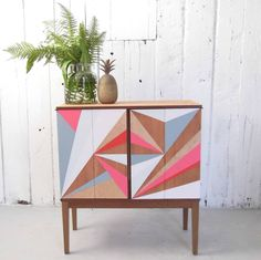 Gold Flash A fabulous drinks cabinet in Teak. Hand painted with flashes of grey, pink, gold and pale blue.We hunt for mid century furniture and can create a special design just for you. We'd love to hear your ideas.We have created a one off drinks cabinet to house your precious gin and spirits stash. This striking cabinet will definitely bring some colour fireworks to your home, and become the centre of lots of fun evenings. Open the doors to reveal all of your bottles framed in the old…