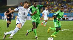 Edin Dzeko of Bosnia and Herzegovina and Kenneth Omeruo of Nigeria compete for the ball