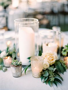 Trios of thick pillar candles at varied heights with clusters of greenery and pops of ivory spray roses. Gold mercury glass votives will be tucked into the greenery to add extra glow...STEMS Floral Design + Productions | Barr Mansion | Stephanie Hunter Photography