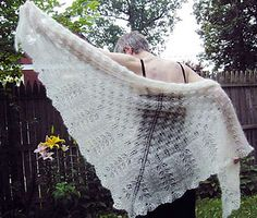 A triangle shawl in two sizes featuring multiple stitch patterns, including a scalloped hem. The triangle is knitted from the center back neck outward.