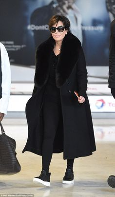 Stylish momma: Kris was pictured wearing a long black coat, which had an oversized furry collar, worn with black leggings and trainers which had a contrasting white sole