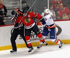CHICAGO, IL - OCTOBER 11: Cal Clutterbuck #15 of the New York Islanders checks Duncan Keith #2 of the Chicago Blackhawks into the referee at the United Center on October 11, 2013 in Chicago, Illinois. The Blackhawks defeated the Islanders 3-2. (Photo by Jonathan Daniel/Getty Images) Blackhawks Hockey, Chicago Blackhawks, United Center, New York Islanders, Referee, Chicago Illinois, Espn, Nhl, Christmas Sweaters