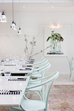 Me encantan las sillas de color verde agua, todo blanco y el olivo en el fondo