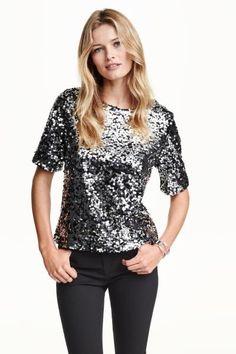 Blouse brodée de paillettes: Blouse courte en mesh brodé de paillettes. Encolure plutôt large. Doublée jersey.