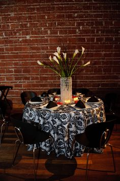 A classic and modern table with a crystal covered vase holding calla lilies and black twigs surrounded by votive candles and roses on a black and white damask linen