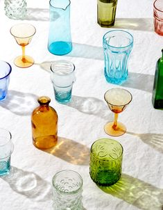 Colored Glassware with Long Colorful Shadows on White Linen