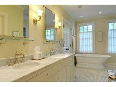 The master bathroom. Note the small pieces of art that are placed above the towel rod and between the windows – small but important touches.