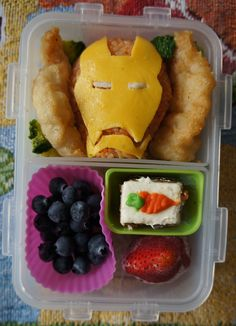 Jack's lunch, day 9: Iron Man grub for our Iron Manong :D (aka leftovers fr yesterday's party!) Brown rice mixed w banana catsup, scrambled egg face and white rice eyes; fish fingers w broccoli; blueberries and strawberry w carrot cake