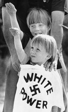 """FILE - In this April 20, 1980 file photo, two boys raise their arms as an adult holds a """"White power"""" T-shirt in front of them during a rally near Benson, N.C. Dozens of Nazis, Ku Klux Klansmen and right-wing sympathizers attended the rally. Historian David Cunningham says the KKK dwindled to nearly nothing during the 1970s and '80s. (AP Photo/Bob Jordan, File)"""