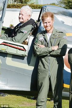 He beams as he folds his arms in front of Tom Neil's plane