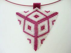 A beautiful peyote triangle pendant! Made of Japanese delica beads in silver lined crystal, white and fuchsia lined amethyst & Swarovski Elements