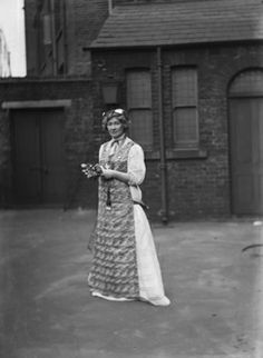 An unidentified suffragette in a long pinafore holding a bunch of flowers.  Christina Broom was a professional photographer who produced a series of London street views for sale as postcards. She later photographed the activities of the suffrage movement in London and is considered one of the earliest female press photographers  c.1910