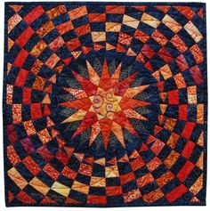 """Whirling Star"" by Judy Mathieson for AAQI: ""One of my favorite stars and an expanding checkerboard setting with machine quilted points overlaying the pieced star."" Made with cotton batiks."