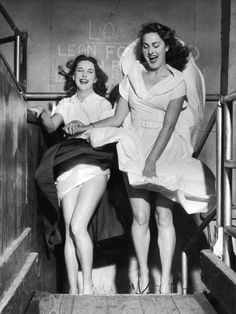 Valerie Carton and Patricia Webb are surprised by a  revealing gust of wind in the funhouse, at London's Battersea funfair. Photo by Carl Sutton,  20th June 1953