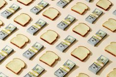 slices of bread and stacks of $100 bills on peach background