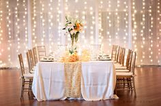 Wall of light. Penny Toilolo used this concept at a wedding with patterned sheer material and the effect was gorgeous!