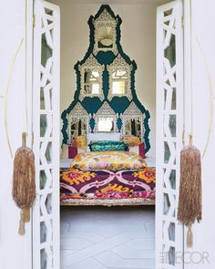 dramatic + exotic details. stacked mirror headboard, ikat bedding, and hand-crafted moroccan french doors.