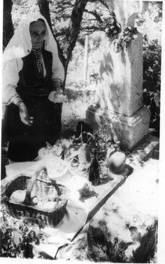 Ilinden: old Orthodox woman arranging food on grave, bread, sheep cheese and rakija (plum brandy)..  Village: Labuniste  Date: 1962 Aug.