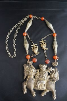 The silver necklace with its all important charm is given to a bride from her mother in law. The charm with the boy on the qilin carrying a lotus is a pictorial pun symbolizing the wish to have a baby boy year after year. It is a charm for fertility. Other auspicious symbols in the necklace are found in the other beads or ornaments, one is a bat, the others are the two three legged toad. They are symbols of wealth and riches. The other beads are long six sided beads with beautiful engraved…