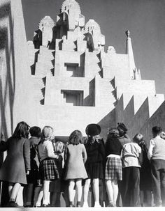 A group of children gaping up at huge, wooden tower sculptures at the Golden Gate International Exposition on Treasure Island in the San Francisco Bay. Photograph by Alfred Eisenstaedt. San Francisco, California, November 1938.