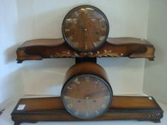 """Two HERMLE German Tambour Mantle Clocks: Glass Bezel with Brass Roman Numerals. Mahogany Cabinet with Gloss Finish. Keywind Movement with Keys. Movement Labeled FSH Germany. Serial Numbers 1356/3 and 1/60/6. 24""""W. One with Carved Scroll Corners and the Other with Applied Acanthus Leaf Sprays. (200-300)"""